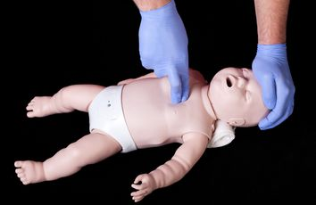 A student practising resuscitation on a plastic baby phantom